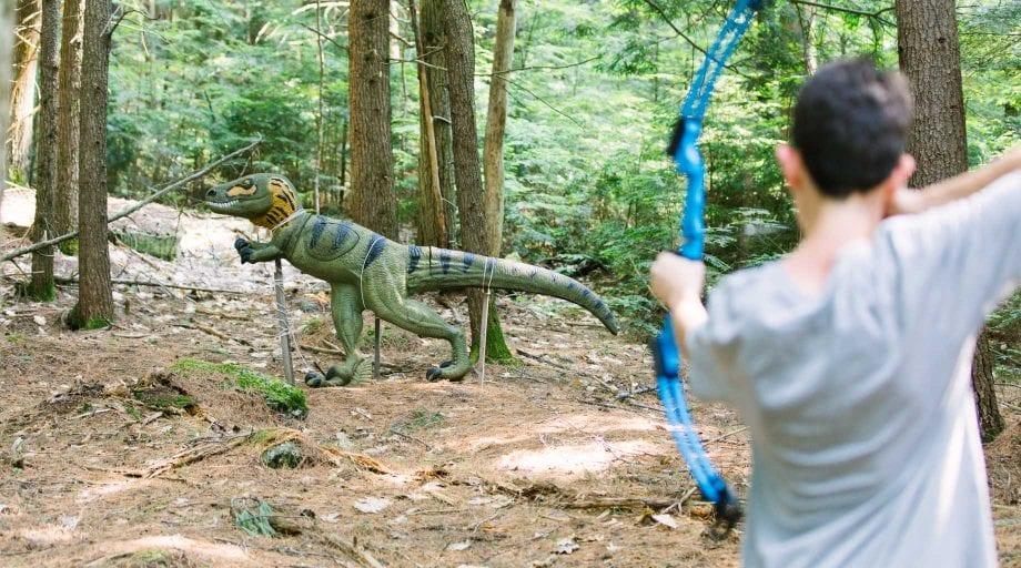 Boy shooting a dinosaur sculpture in 3D archery