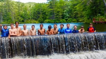 Boys lined up by small waterfall