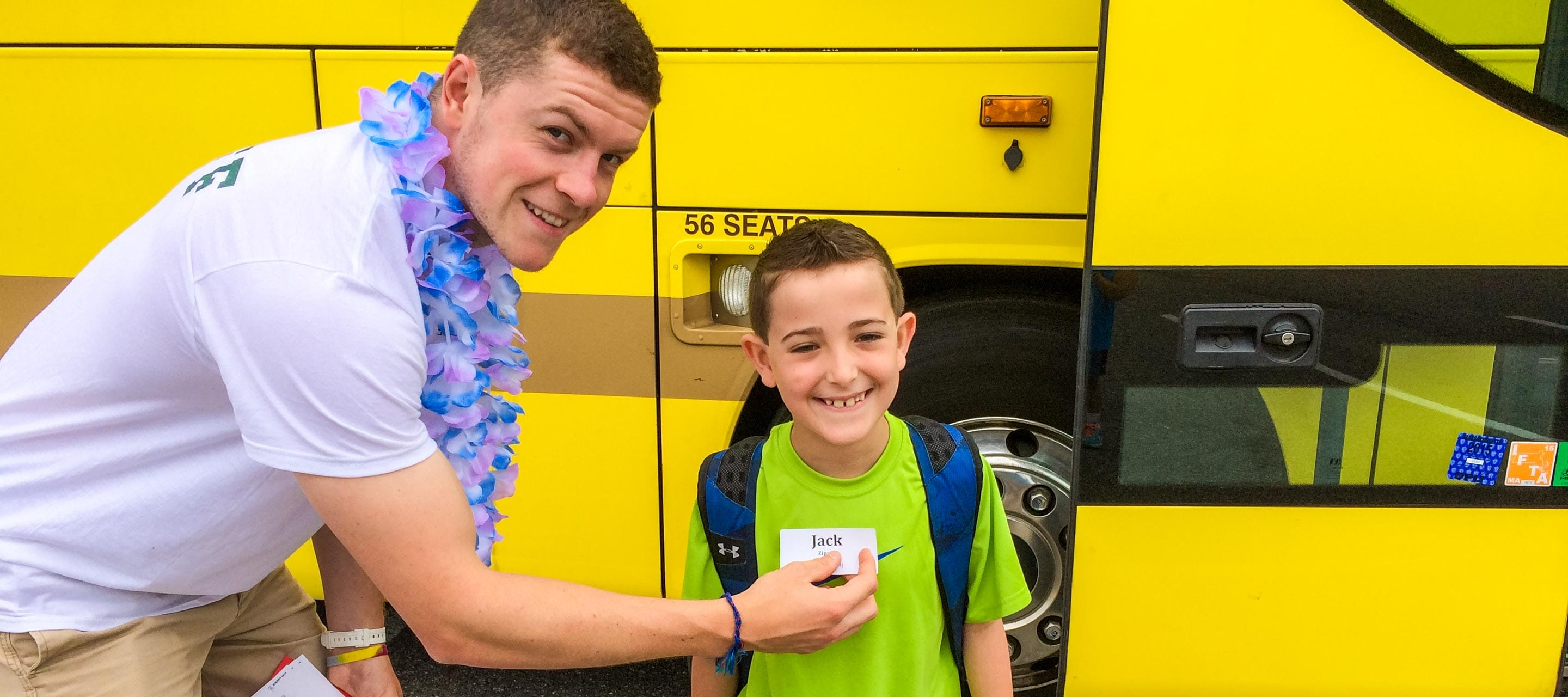 Putting name tag on camper by school bus