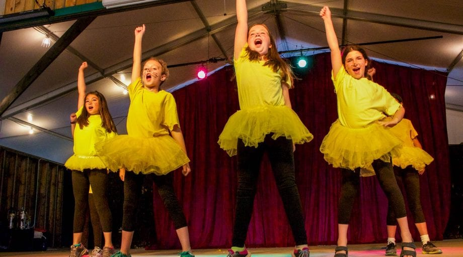 Campers in yellow and black dancing on stage