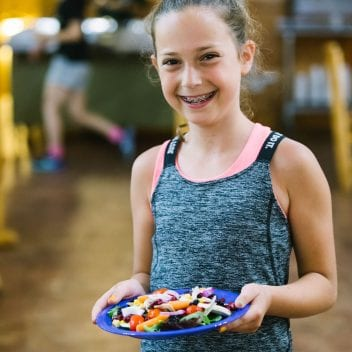 Young female camper holding a plate with veggies