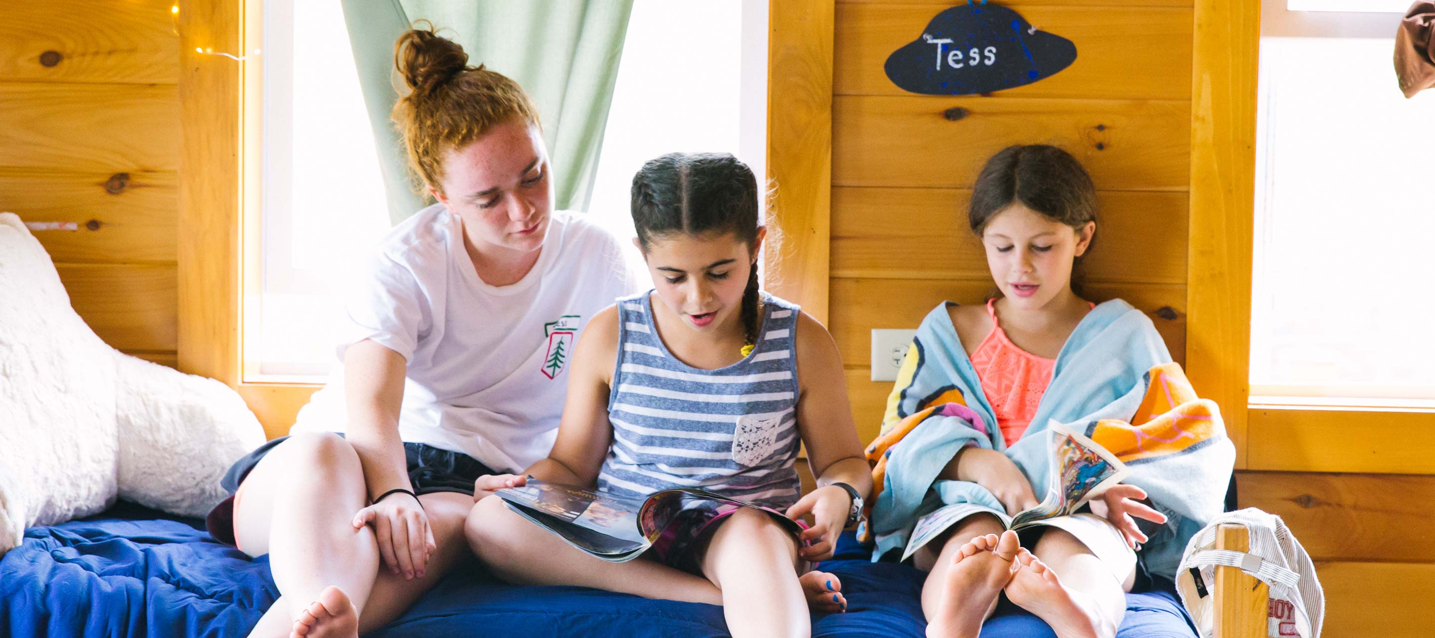 General Counselor in girls bunk reading with campers