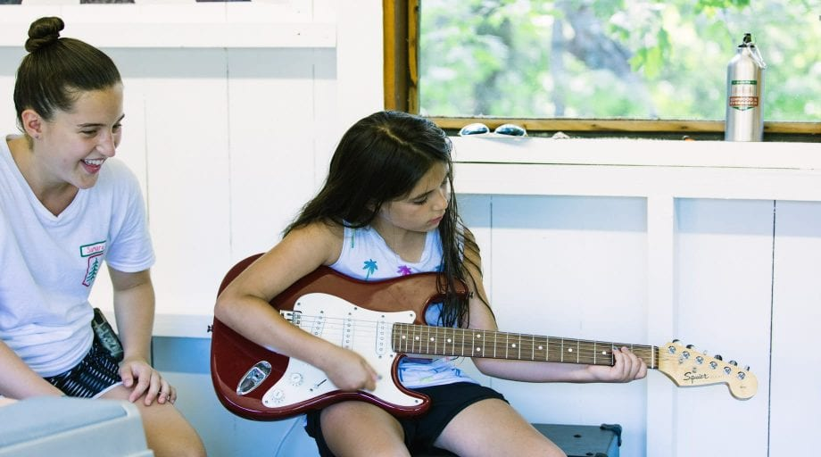 Girl playing guitar indoors