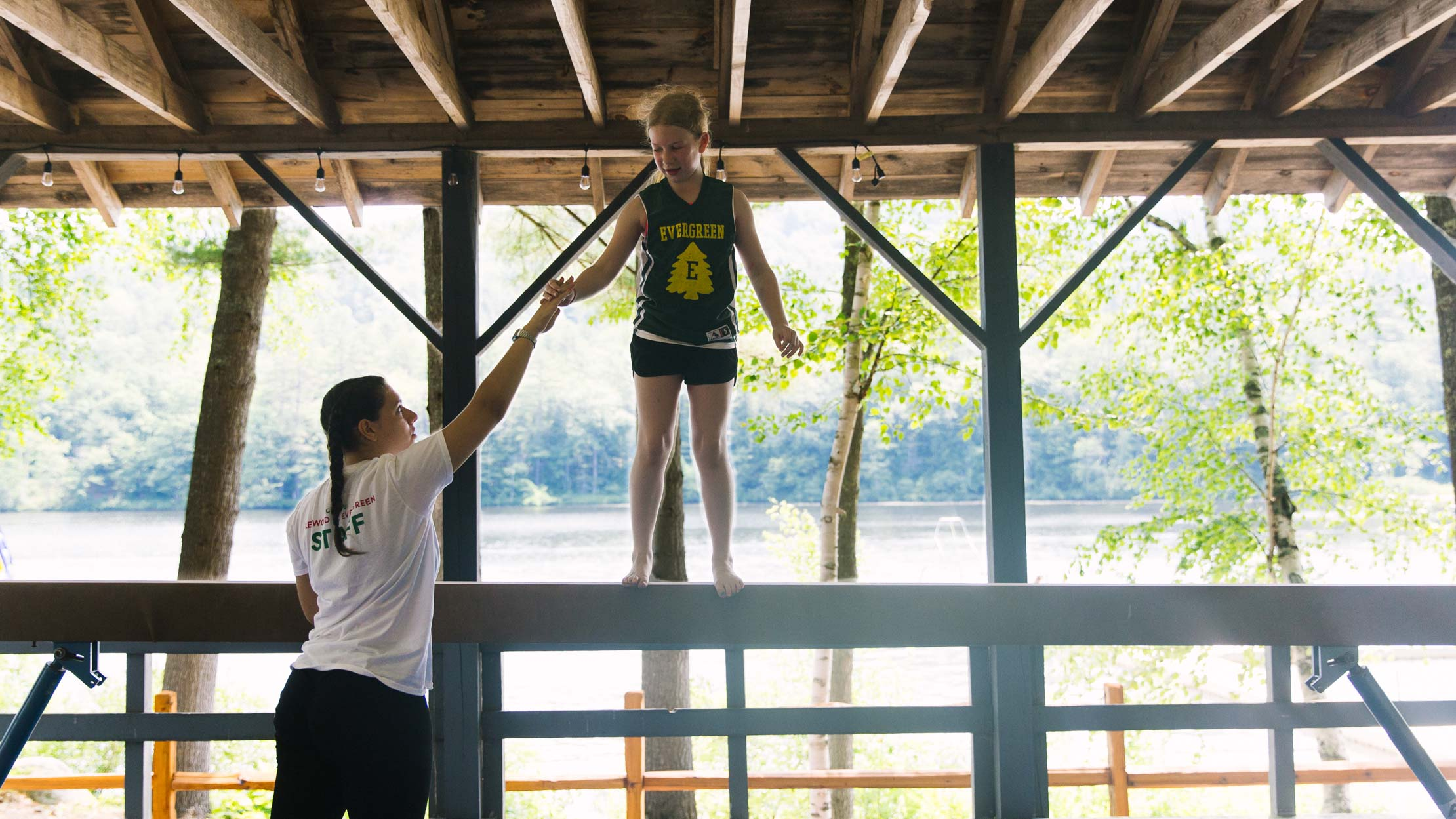 Gymnastics instructor helping camper on balance beam
