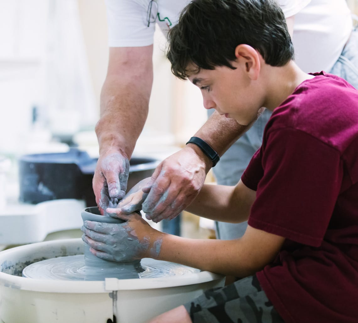 Camper learning pottery wheel with instructor's help