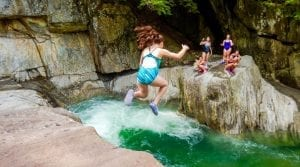 Girl jumping into waterhole during an outdoor adventure trip
