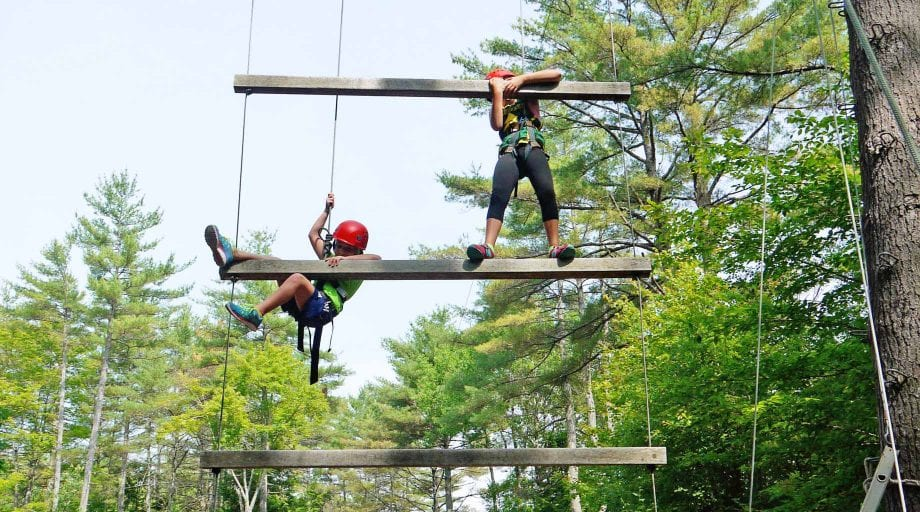Girls on high ropes course ladder
