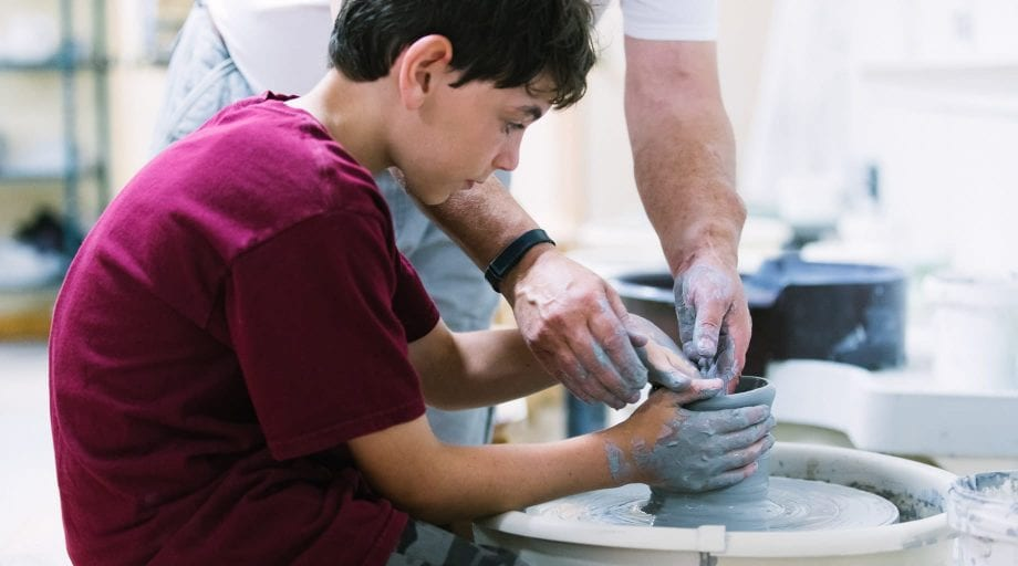 Boy learning how to use the spinning wheel in ceramics