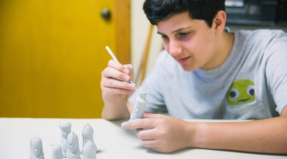 Boys painting ceramic figurines