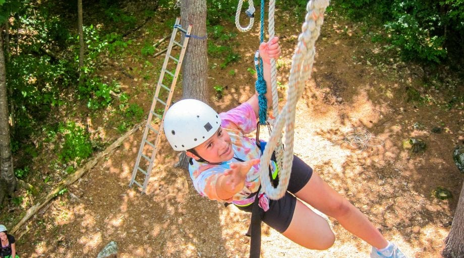 Girl reaching for rope on high ropes course