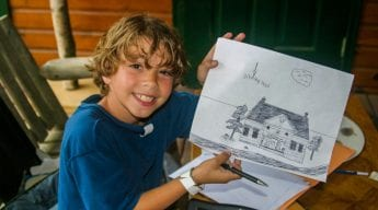 Boy showing off drawing of camp