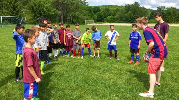 Soccer instructor with campers in a circle