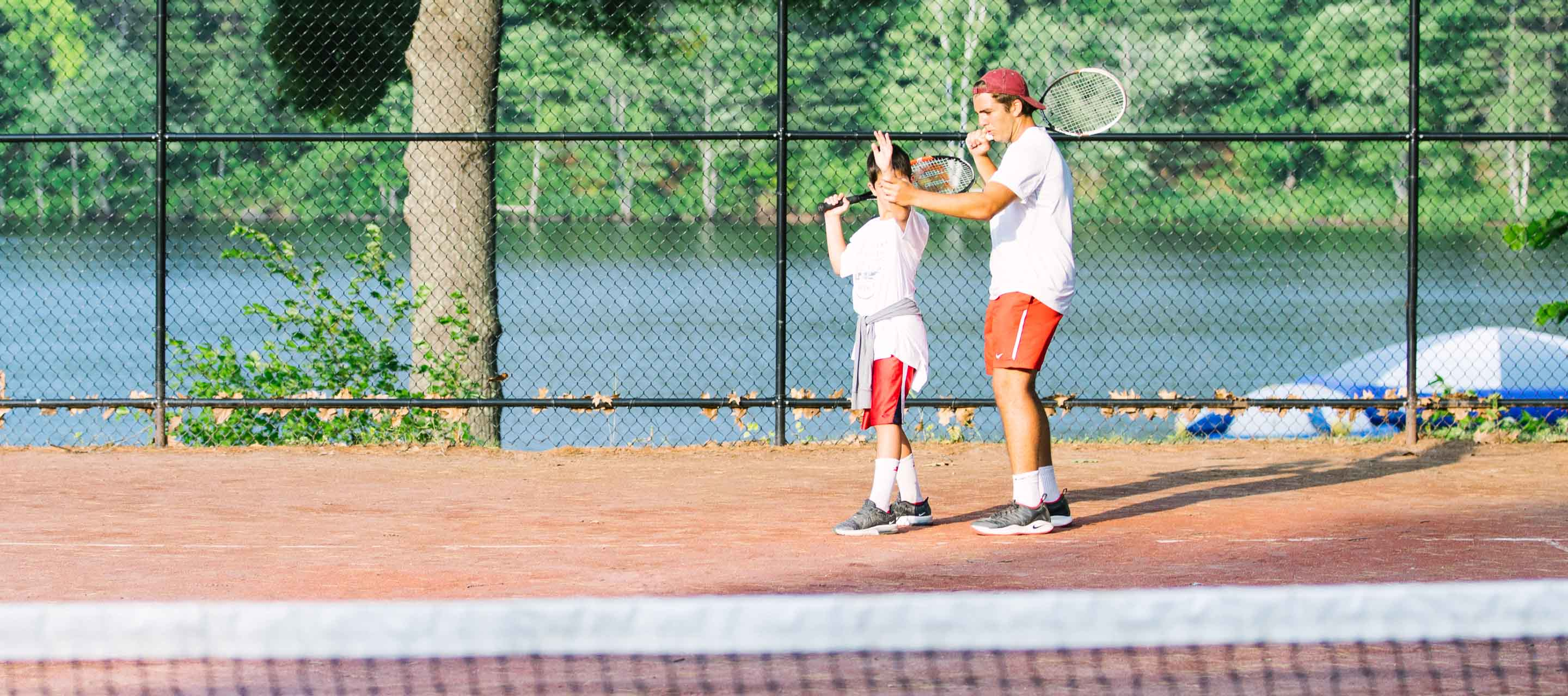 Tennis specialist teaching camper how to serve