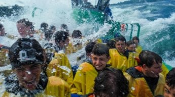 Boys on boat in yellow rain jackets getting splashed by waves