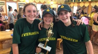 Three girls smiling with trophy