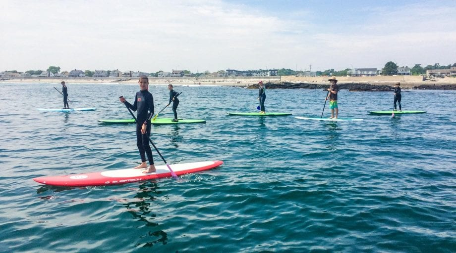 Campers on stand up paddleboards on ocean