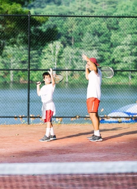 Staff teaching male camper tennis