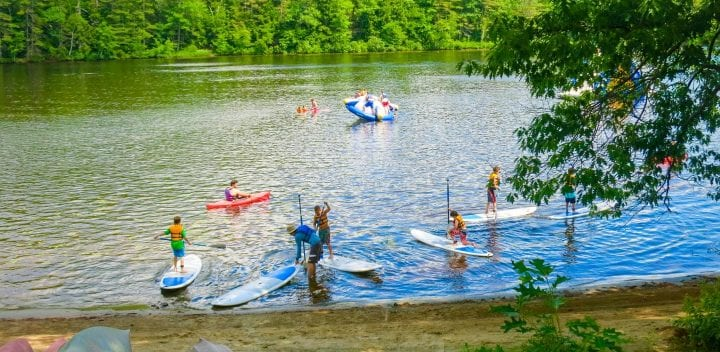 Campers on stand up paddle boards and kayaks