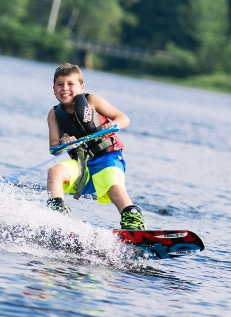 Boy wakeboarding on lake