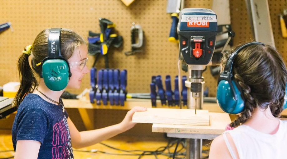 Girls at woodworking with drill