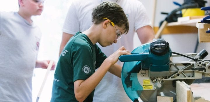 Boy cutting woodworking project with a saw
