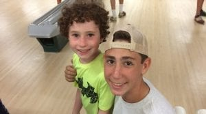 Big brothers smiling at a bowling alley
