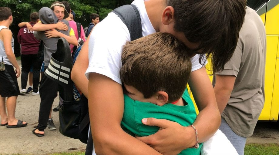 Big brother hugging camper