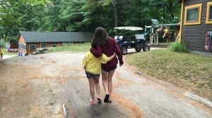 Camper and big sister walking with arms around each other's waists.