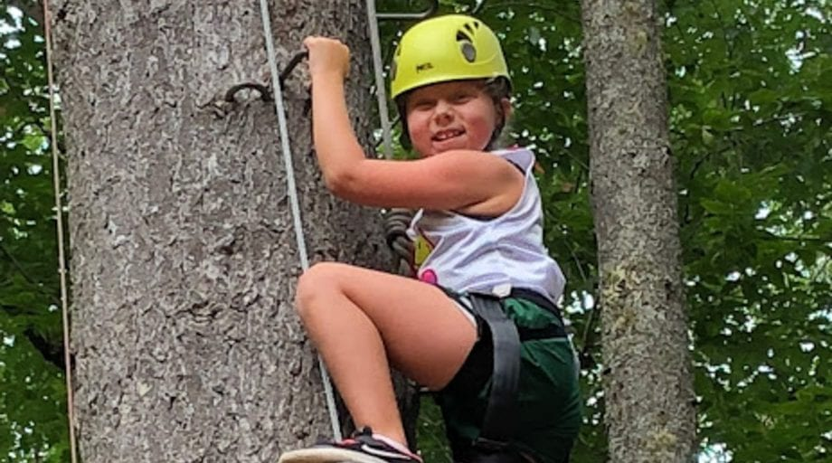Girl on high ropes course climbing a tree
