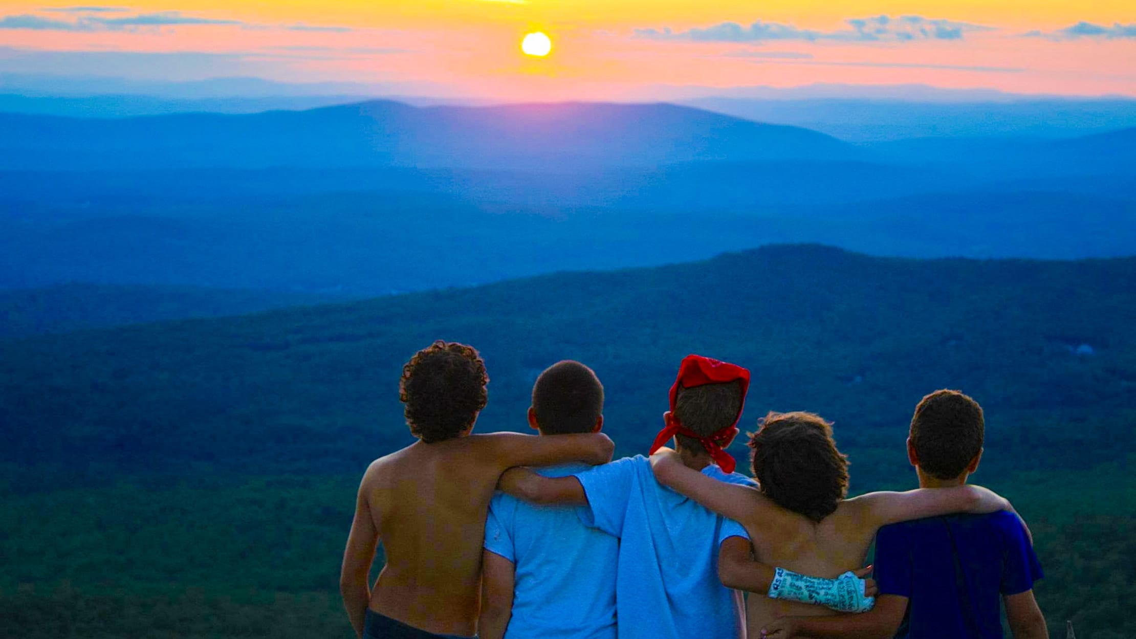 Boys on mountain admiring sunset
