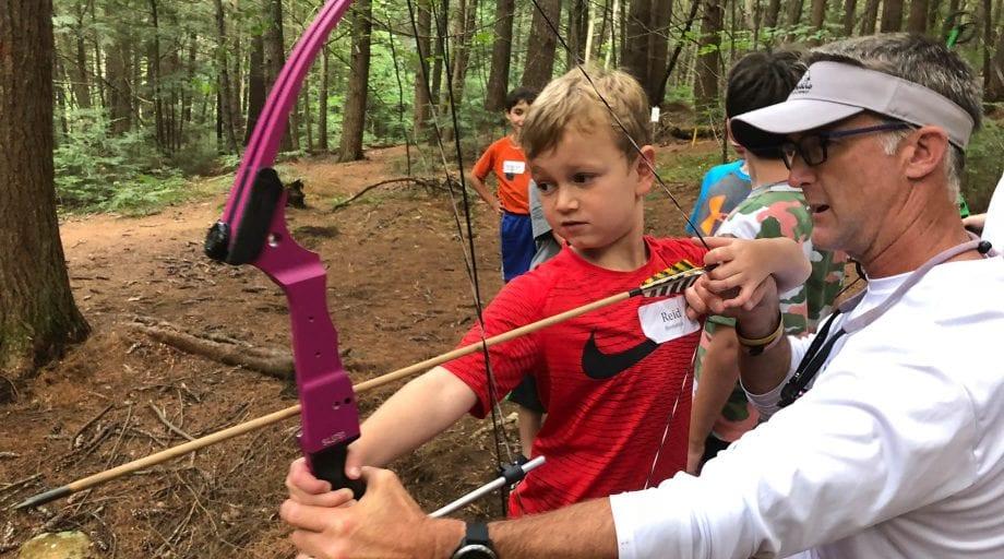Boy learning archery on Rookie Day