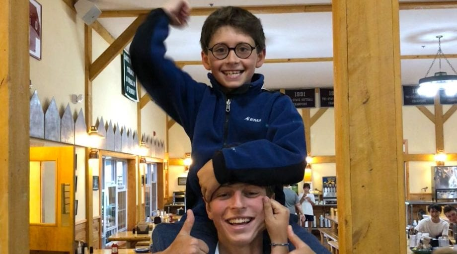 Camper on staff's shoulders in dining hall