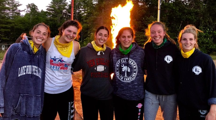 Teens smiling by fire with bandanas on