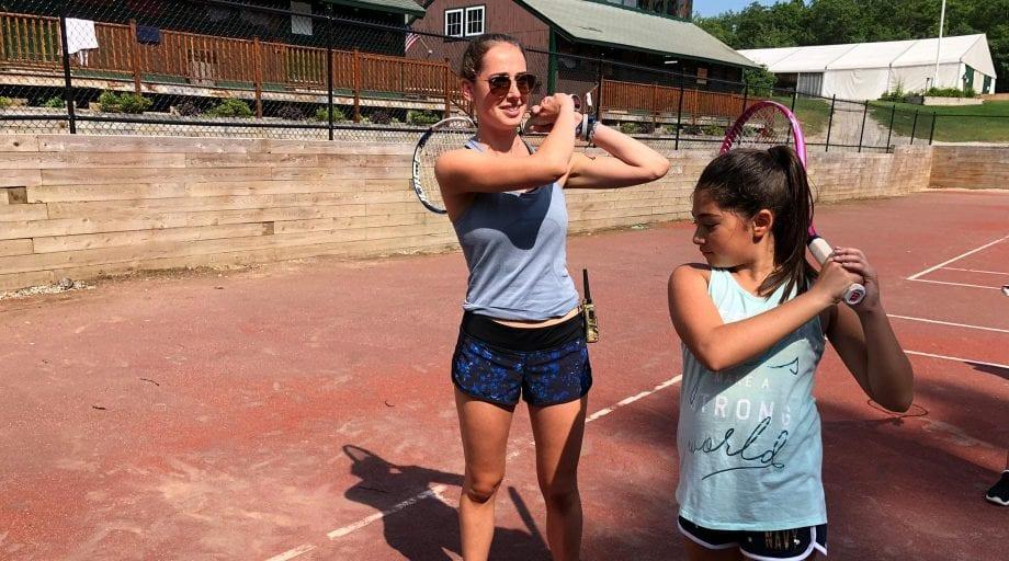 Staff teaching camper tennis